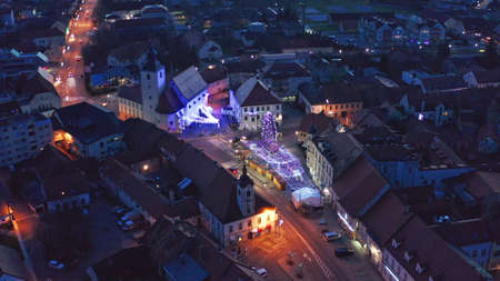Aerial view of Christmas fair and sparkling decorative lights on main square in Slovenska Bistrica, a small medieval town in Slovenia