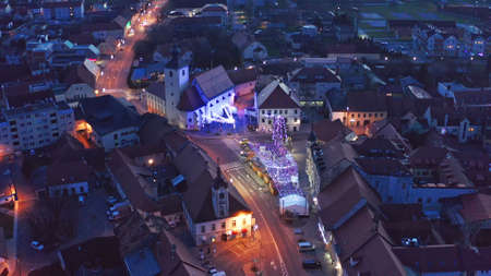 Slovenska Bistrica, Slovenia - Dec 25 2019: Christmas fair on main square in Slovenska Bistrica, a small medieval town in Slovenia, aerial view of town center with shops and bright xmas lights Редакционное