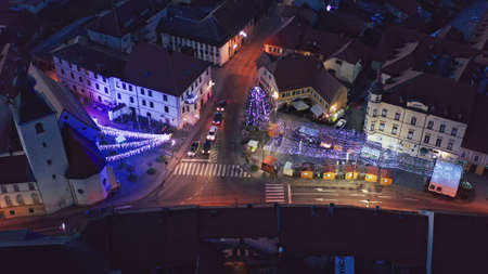 Slovenska Bistrica, Slovenia - Dec 25 2019: Aerial view of Christmas fair on main square in Slovenska Bistrica, a small medieval town in Slovenia, decorative lights illuminate the streets Редакционное