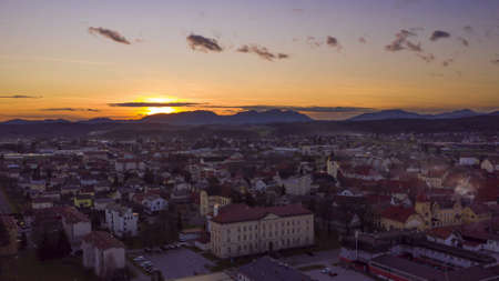 Aerial hyper-lapse of sunsest above a small historic town in Europe, tranquil cityscape in twilight, sundown behind mountains in far background Stockfoto
