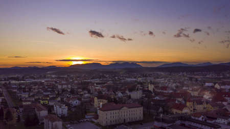 Sunset time-lapse, aerial view of historic town in Europe with mountains in the background, sundown behind mountains in far background, steady shot