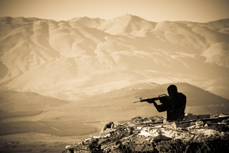 vintage military rifle: A figure of a Shooting Man  with a mountainous backdrop Stock Photo