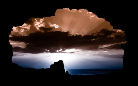 cueva: puesta de sol enmarcado en una entrada de la cueva Foto de archivo
