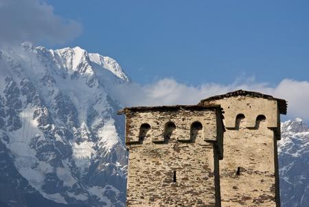 svan: due svan torre whith monte Shkhara in background - ushguli, georgia