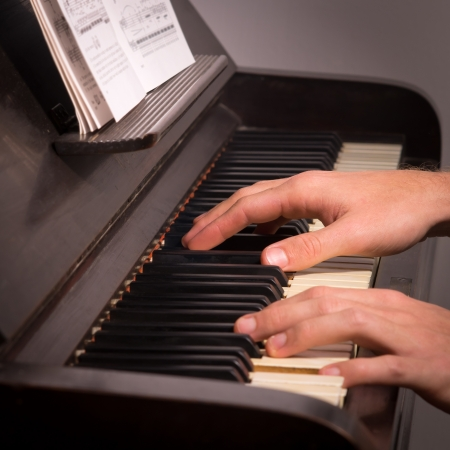 a photo of a man playing on a piano photo