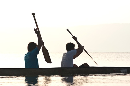 Two men paddling in a canoe at the sea of Galilee  photo