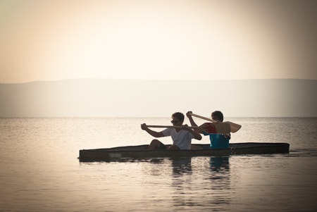 holyland: Two men paddling in a canoe at the sea of Galilee
