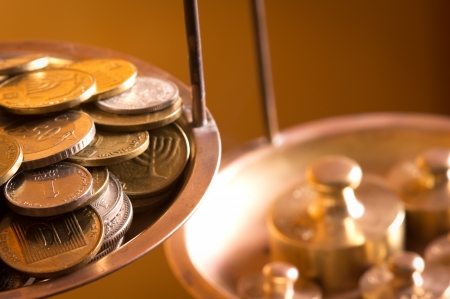 cost estimate: vintage scale wheights outweigh coins on an old balance Stock Photo