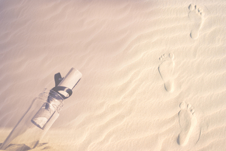 footprints on a sand dune with a message in a bottle photo