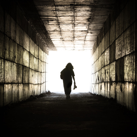 silhouette of a person reaching the light at the end of the tunnel 版權商用圖片