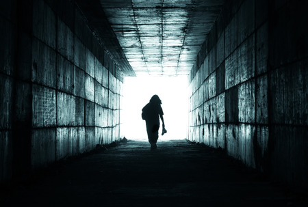 silhouette of a person reaching the light at the end of the tunnel Stock Photo