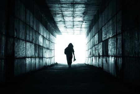 hombre solo: silueta de una persona llegar a la luz al final del túnel