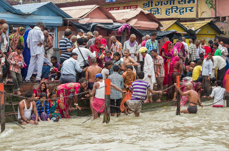 ghat: HARIDWAR, INDIA - AUG 29 2014: Devotees gathered to make a holy dip at river Ganges Editorial