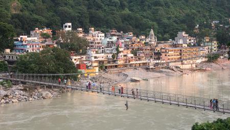 tera: RISHIKESH, INDIA - AUG 30, 2014: Unidentified People crossing Laxman Jhula footbridge on river Ganga by the Tera Manzil Temple at sunset.