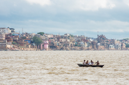 ghat: VARANASI, INDIA - SEPTEMBER 2, 2014: Unidentified people sailing in a boat on the the Ganges river