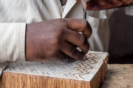 a craftsman carving a wooden printing block for textile block printing Stock Photo