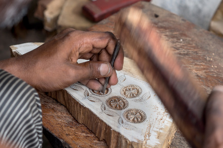 a craftsman carving a floral pattern on a wooden printing block for textile block printing at the village of Sanganer, Rajasthan - india Stock Photo