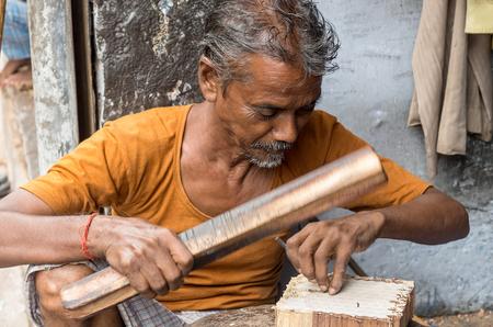 SANGANER, INDIA - SEPTEMBER 11, 2014: Unidentified craftsman carving a wooden printing block for textile block printing