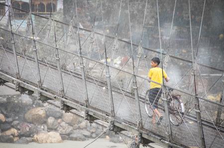 tera: RISHIKESH, INDIA - AUG 28, 2014: Unidentified boy crossing Laxman Jhula footbridge on bicycle in the monsoon rain