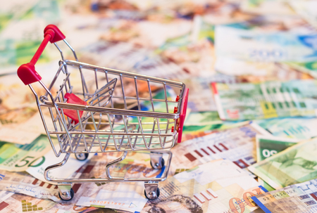 israeli: red shopping cart for shopping stands on banknotes money.