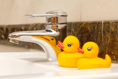 rubber ducks sitting by sink tap photo
