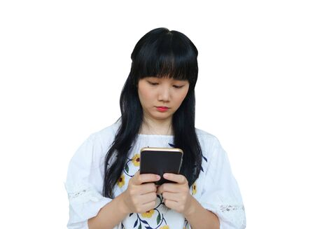 Cute Asian Girl Using Mobile Phone with Serious Face. isolated on White Background. Reklamní fotografie