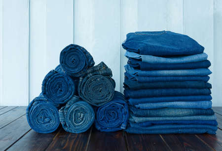 jeans stacked on wooden floor. blank background for design and text input. Фото со стока