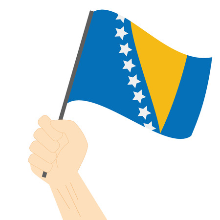 Hand holding and raising the national flag of Bosnia and Herzegovina