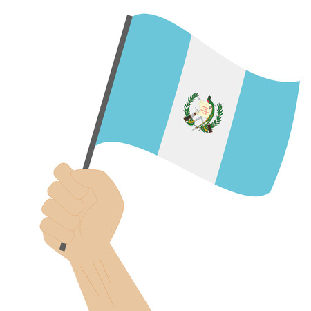Hand holding and raising the national flag of Guatemala