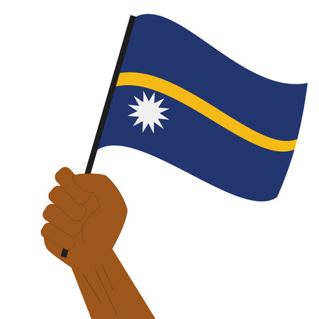 Hand holding and raising the national flag of Nauru