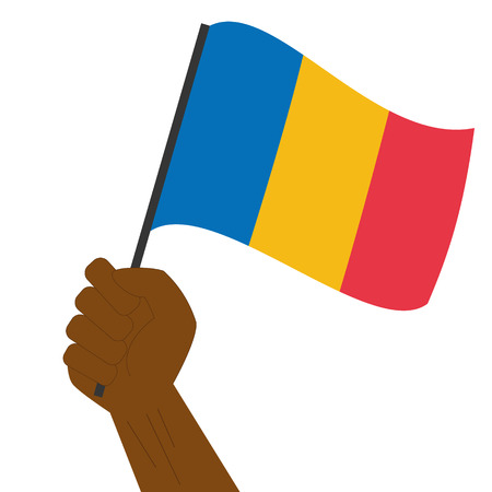 Hand holding and raising the national flag of Chad
