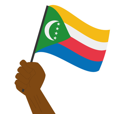 sovereignty: Hand holding and raising the national flag of Comoros