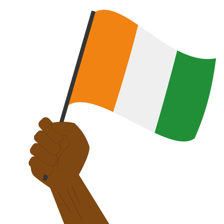 Hand holding and raising the national flag of Cote d´Ivoire