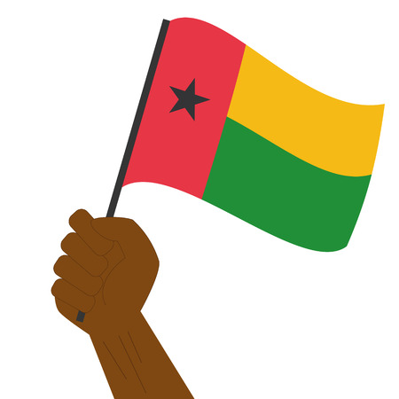 Hand holding and raising the national flag of Guinea Bissau