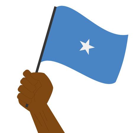 Hand holding and raising the national flag of Somalia