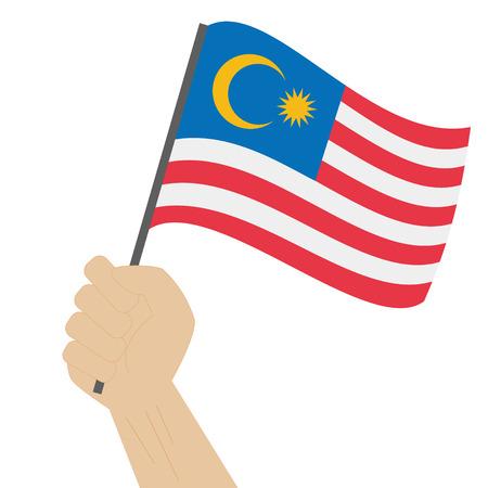 Main tenant et levant le drapeau national de la Malaisie