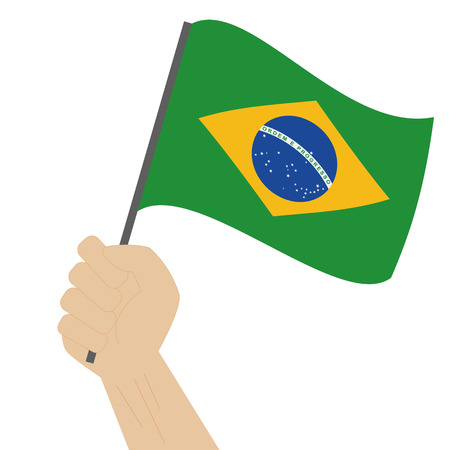 Hand holding and raising the national flag of Brazil