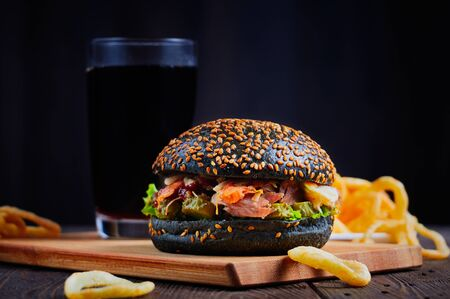Black burger on wooden cutting board isolated on black background.