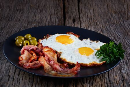 Fried eggs with bacon on a wood plate on a black background.