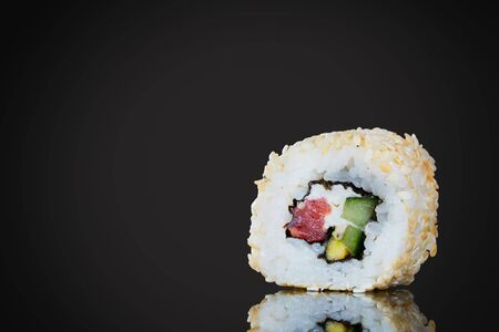 Sushi with red fish and avocado, close-up, on a black background. Japanese traditional cuisine, delicious sushi with dill and sesame seeds. Tasty rolls - California and Philadelphia.