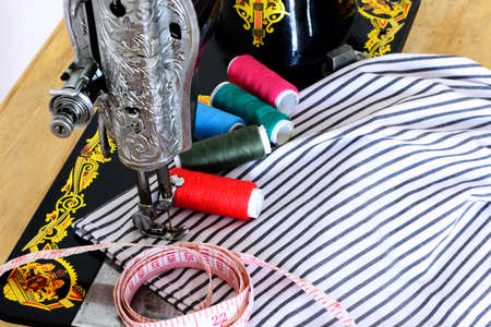Close up image of sewing machine with colored threads and sartorial meter  Stock Photo