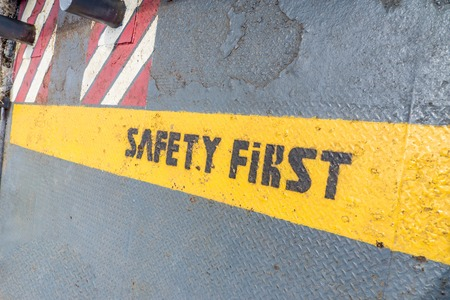 safety first: Safety First sign on caution strip. Stock Photo