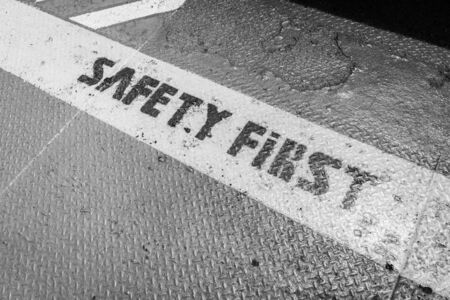safety first: Safety First sign on caution stripblack and white.