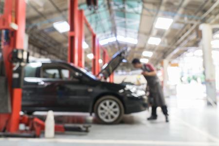 Fahrzeugtechniker die Reparatur des Autos in der Garage Hintergrund verschwommen.