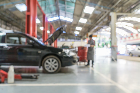 automobile workshop: Blurred of car technician repairing the car in garage background. Stock Photo