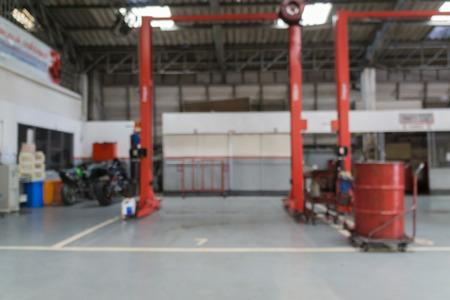 Borrado de técnico de carro reparando o carro no fundo da garagem. Imagens
