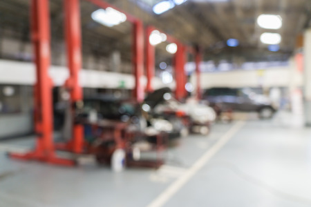 automotive repair: Blurred of car technician repairing the car in garage background. Stock Photo