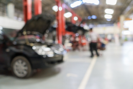 car lift: Blurred of car technician repairing the car in garage background. Stock Photo