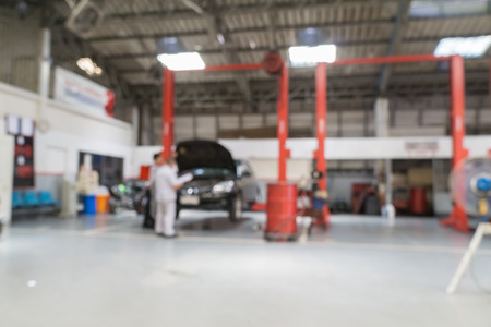 auto lift: Blurred of car technician repairing the car in garage background. Stock Photo