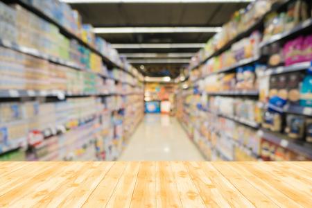 Holztischplatte mit Blurr Hintergrund: Supermarktgeschäft und Unschärfe Hintergrund mit Bokeh - für Montage oder verwendet angezeigt werden Ihre Produkte werden